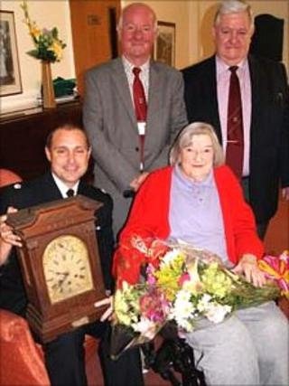 Bettie Lewis hands over the clock
