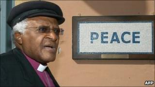 """Desmond Tutu walks past a street mosaic which reads """"Peace"""" on the green line that separates the Greek Cypriot side from the Turkish military-controlled areas in the heart of Nicosia (2008)"""