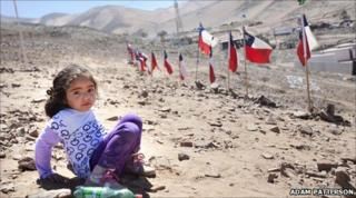 Young girl playing on hillside overlooking Camp Esperanza
