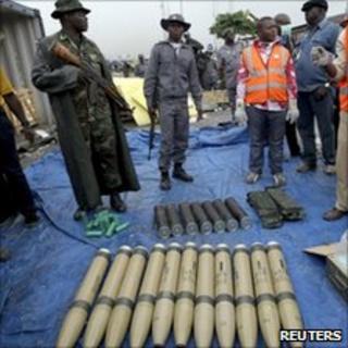 Security officials stand around some of the illegal weapons found at Nigeria's main seaport in Lagos on 27 October 2010