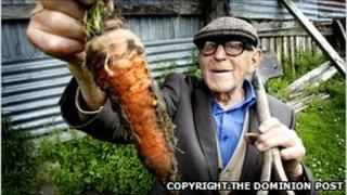 Man holding up a carrot