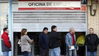 People waiting to enter a job centre in Madrid