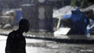 A man walks in the rain in the Haitian capital, Port-au-Prince, on 31 October