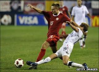 Adam Matuszczyk of Poland holds off Stuart Holden of the US during October's game in Chicago