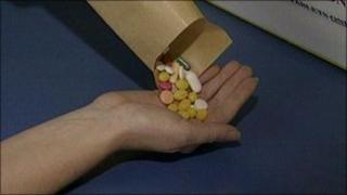 Person pouring pills from envelope