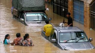 Residents wade through flood water in Hat Yai, southern Thailand, on 3 November 2010