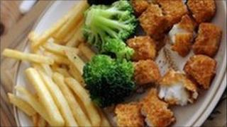 Dinner plate of nuggets and chips and broccoli