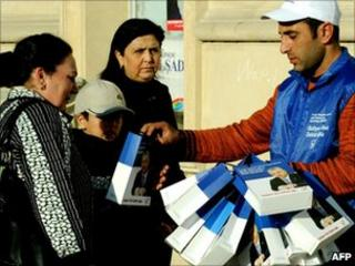 Party worker hands out election material in Baku