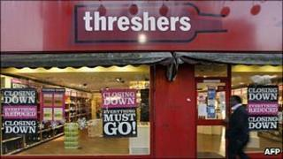 Man walks past a Threshers store
