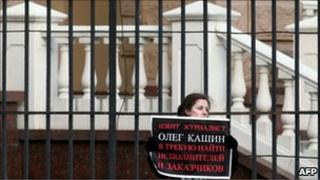"A woman holds a poster reading ""Journalist Oleg Kashin has been beaten. I demand to find the persons who attacked him"" during a picket at the headquarters of Moscow police department in Moscow on November 7, 2010"