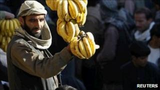 A man shows bananas for sale at a market in Kabul on 8 November 2010