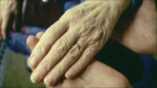 Elderley patient and helper hold hands