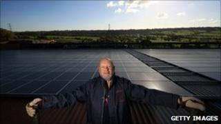 Michael Eavis stands in front of his solar panels