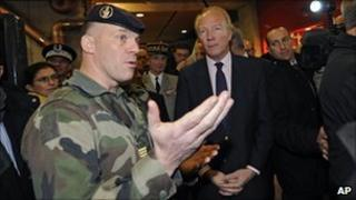 French Interior Minister Brice Hortefeux listens as a soldier speaks at Montparnasse railway station in Paris, 10 November