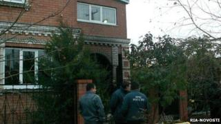 Emergency workers stand outside the house where the murdered occurred
