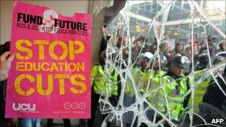 A Demonstrator holds a placard next to a broken window at 30 Millbank