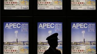 Policeman stands in front of Apec signboard in Tokyo on 10 November 2010