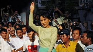 Aung San Suu Kyi waves to supporters as she arrives at NLD headquarters in Rangoon