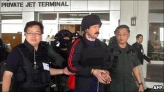 Viktor Bout (centre) is escorted to a plane at Bangkok's Don Mueang airport, Thailand, 16 November 2010
