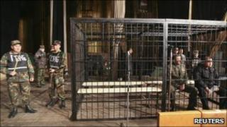 Baktybek Kalyev (R), former defence minister, and ex-deputy chief of security Nurlan Temirbekov sit in a metal cage during a court session