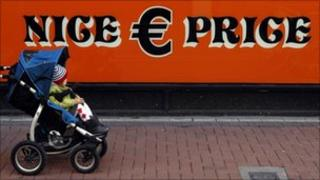 Child being pushed past a discount store in Dublin