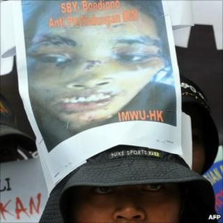 A member of Migrant Care Indonesia wears a picture of Sumiati Binti Salan Mustapa on her hat during a protest at the Saudi Arabian embassy in Jakarta
