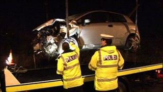 Crashed car being examined by two police officers