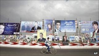 An Afghan youth rides his bicycle past election posters in Kabul on 5 September 2010