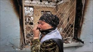 An ethnic Uzbek woman cries as she passes a ruined house in Osh (June 2010)