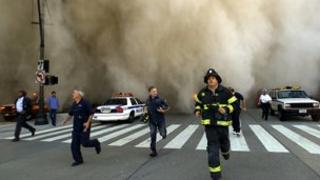 Rescue workers run from approaching dust and ash