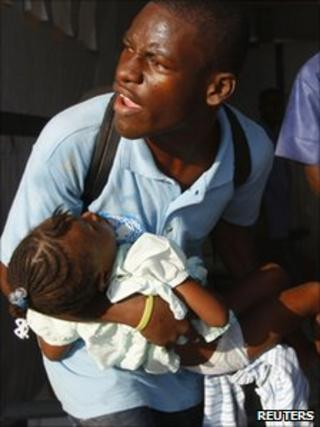 A man carries a child with symptoms of cholera to receive treatment in a clinic set up by International Red Cross in Port-au-Prince (24 November 2010)