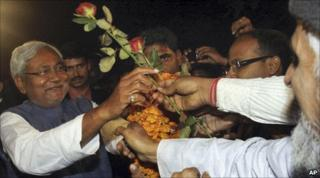 Nitish Kumar accepts flowers from supporters after his election victory in Patna, on 24 Nov 2010