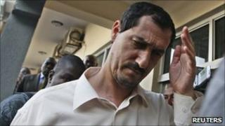 Azim Aghajani, an Iranian charged with attempting to import prohibited arms into Nigeria, walks outside a magistrate court in Abuja, 25 November 2010