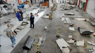 A picture taken on July 24, 2009 shows investigators looking at debris from the mid-Atlantic crash of Air France flight 447 at the CEAT aeronautical laboratory in Toulouse, southern France