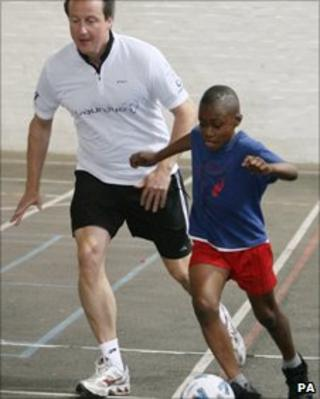 David Cameron playing football during a visit to a London school in 2009
