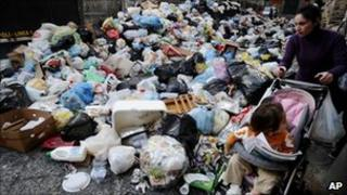 A woman pushing a baby stroller makes her way through uncollected rubbish in Naples, Italy, 22 November 2010