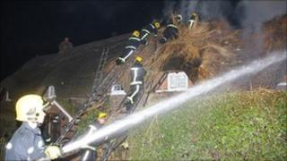 Firefighters tackling thatch fire