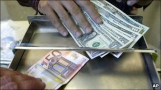 A money changer employee changes Euro and US Dollars on an exchange kiosk