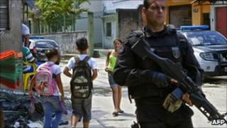 An armed policeman patrols the Complexo do Alemao shantytown in Rio de Janeiro as children walk past