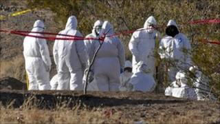 Forensic workers at the site where 18 bodies were found in mass graves near Ciudad Juarez, northern Mexico