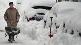 A man tries to clear snow around cars