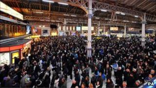 Passengers at Victoria Station in London as bad weather causes delays to train services