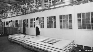 Walls and windows of pre-fabricated houses being painted in a factory in 1950