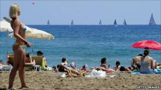 Sunbathers on the beach in Barcelona (with a yacht race going on in background), July 2010
