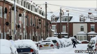 A man shovels snow from around his car on a street in Goole
