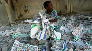 A child plays among election ballots at the site of a polling station in Port-au-Prince (29 November 2010)