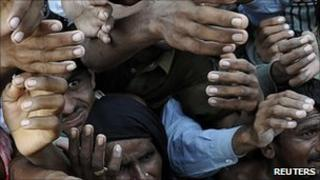 Flood victims raise their hands to receive food in the Dera Ghazi Khan district of Punjab province on 21 August 2010