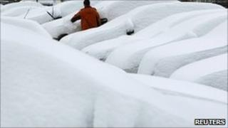 A man scrapes snow from a car in a car park at Munich airport, Germany, 2 December