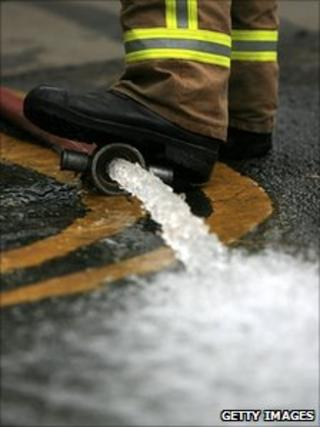 Firefighter's boot on a hose pumping flood water