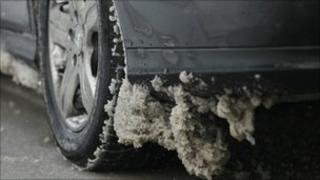 Snow clings to the underside of a car